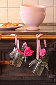 Cyclamen and juniper sprigs in preserving jars hung from old stove