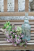 Bunch of flowering oregano next to small glass carafe