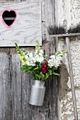 Bouquet of snapdragons in old milk churn hung on door