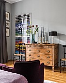 Colourful graphic artwork on wall next to wooden chest of drawers in bedroom