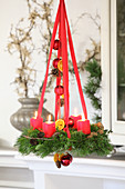 Classic Advent wreath hung from red ribbons