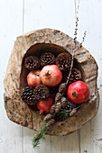 Pine cones and pomegranates in rustic wooden bowl seen from above