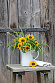 Sunflowers and ornamental grasses in jug on stool