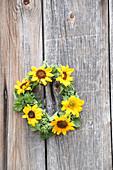 Kranz aus Sonnenblumen auf Holzuntergrund