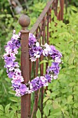 Heart-shaped wreath of hydrangea and phlox flowers on rusty garden fence
