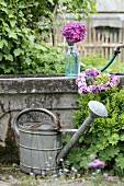 Zinc watering can in front of stone pool decorated with flowers