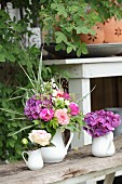 Three jugs holding roses, hydrangeas and a luxuriant summer bouquet