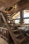 Rustic wooden staircase and trunk in living area of chalet