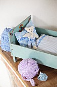 Hand-made bed linen and teddy bear in vintage dolls' bed