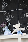Hand-made towelling teddy bear and lavender sachet in front of drawings on chalkboard