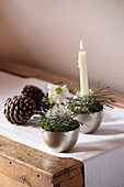 Arrangements of moss, pine needles and silver wire with hellebore and candle in silver bowls
