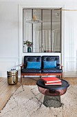 Blue cushions on comfortable, two-seater, black leather couch below interior window