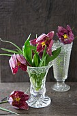 Schachbrettblumen in nostalgischen Glasvasen