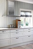 Extractor hood and wood-clad walls in white country-house kitchen