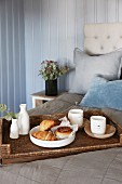 Pastries, cups and vase on wicker tray on grey bedspread