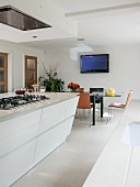 Island counter and dining table in white, modern kitchen-dining room