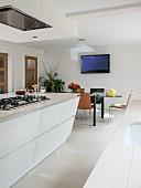 Moderne weiße Wohnküche mit Kochinsel und Esstisch