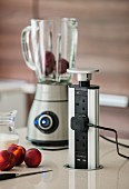 Pop-up multiway power strip and jug blender in kitchen