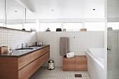 Helles Bad mit weißen Fliesen und eingebautem Waschtischmöbel