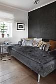 Breite Couch mit Kissen vor schwarzer Wand und Beistelltisch
