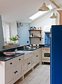 Country-house kitchen with black worksurface, white, double Belfast sink and blue accents
