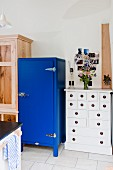 Blue fridge next to white chest of drawers in country-house kitchen