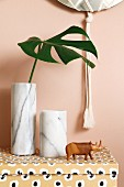 Cheese plant leaf in marble vase next to carved rhino on top of patterned cardboard box