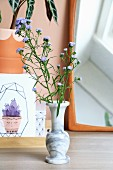 Stems of purple flowers in marble vase in front of mirror and drawing of cactus