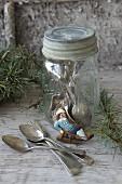 Plätzchen mit Schlittenfahrer lehnt an Schraubglas mit Silberbesteck