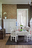 Table and chairs in child's bedroom with brick wall