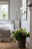 Weißer Flieder im Eimer auf dem Holzboden im Schlafzimmer