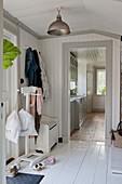 Ländlicher Flur in Weiß mit Dielenboden und Blick in die Küche