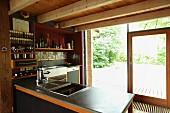 Offene Küche mit Holzbalkendecke und Gartenblick