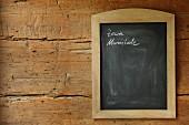 Gerahmte Tafel mit Notizen an rustikaler Holzwand