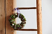 Easter wreath hung on rustic wooden ladder