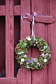 Romantic Easter wreath hung on claret-red garden gate