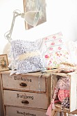 Patchwork cushion and knitting on top of old chest of drawers