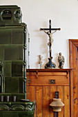 Crucifix on wooden shelf next to green tiled stove