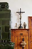 Kreuz mit Jesus auf Holzablage neben grünem Kachelofen