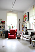 White couch, red armchair and bookcase in study