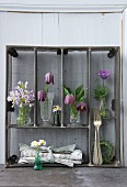 Various spring flowers arranged in upright metal cutlery drawers