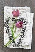 Schachbrettblumen und schwarz verziertes Drahtherz auf Stoffservietten
