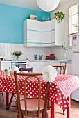 Esstisch mit rot-weisser Tischdecke vor Einbauküche mit dekorierten Hängeschränken