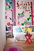 White throw and various scatter cushions on couch in front of colourful wall decorated with large floral motifs