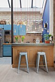 Metal stools at kitchen counter below pendant lamps forming partition
