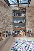 Bookshelves with blue back wall in niche in stone wall
