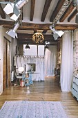 Studio lamps and wooden beams in industrial-style clothes shop