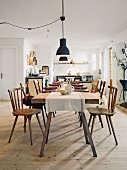 A rustic dining table with wooden chairs in a rural-style kitchen