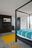 Black bed frame and partition in bedroom with concrete floor