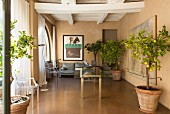 Classic designer items, potted trees and restored wood-beamed ceiling in lounge area